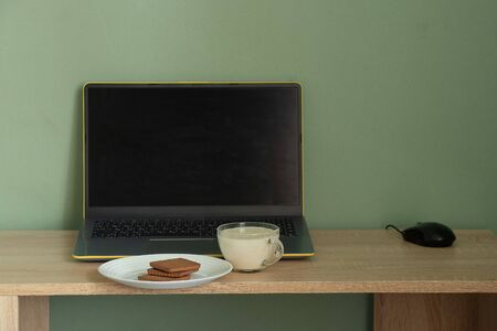 laptop with green screen yogurt with cookies on a table in a room at hom