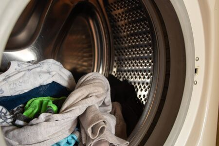 full tank in the washing machine of clean children's clothes after washing 版權商用圖片