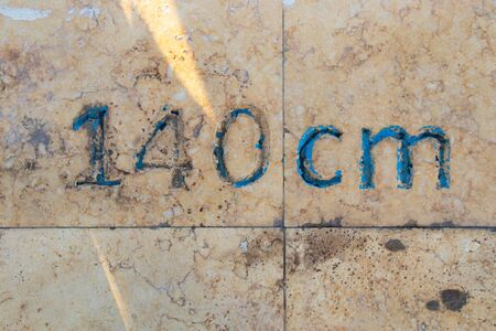 one hundred forty cm number is written on a stone slab Stock Photo
