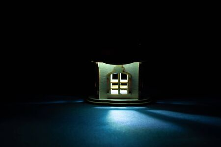light comes out of the window of a wooden house in the dark