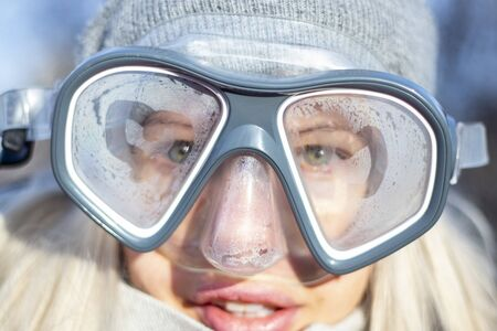 young girl is standing in a mask for diving in winter in the frost on the street, is waiting for a vacation Banco de Imagens