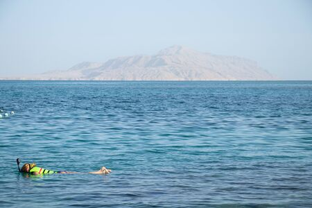girl diving in the red sea in egypt lies on the water in a mask