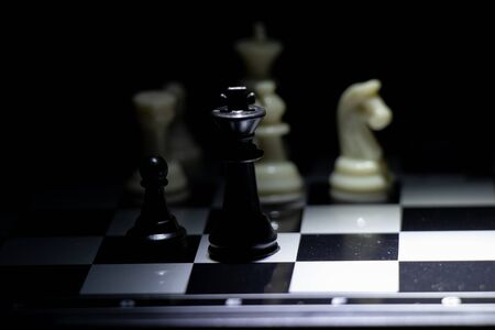 chess pieces on a chessboard in a dark room illuminated by a lantern
