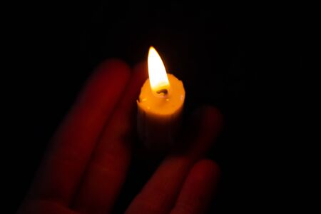 hand holds a burning candle in a dark room