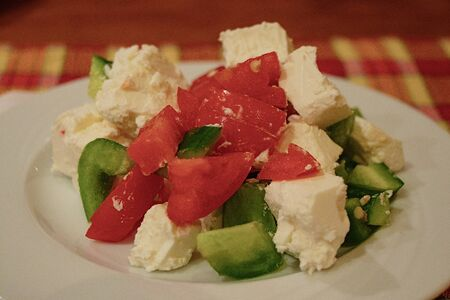 salad with vegetables and cheese on a white plate in the evening in a restaurant