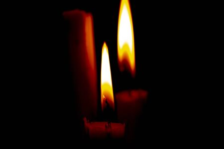 lighted candle stands in a dark room