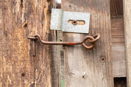 old rusty hook on a wooden gate in the yard