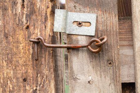 alter rostiger Haken an einem Holztor im Hof