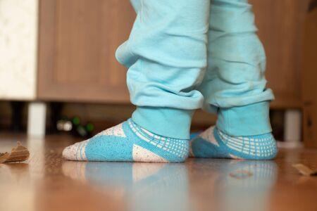 legs of a four year old boy in blue socks on the floor Foto de archivo
