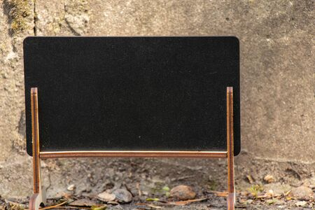 empty little school blackboard with place for text stands outdoors