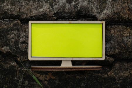 wooden small tv with a yellow screen stands on a tree in the forest, empty space for text