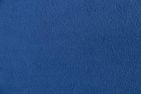 plain dark blue fabric made of artificial materials as a wallpaper
