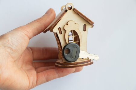 wooden small toy house holds a female hand on a white background