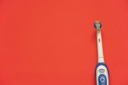 old electric toothbrush on red background