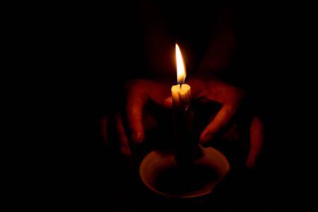 candle flame illuminates a female hand in a room