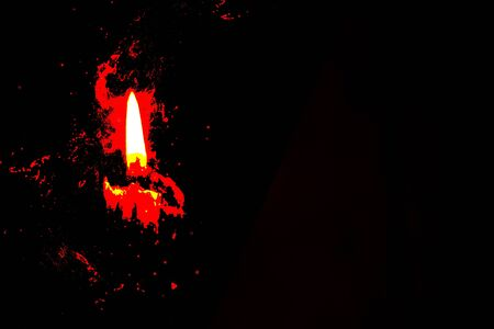 single candle flame on a dark background with red spots of paint, religion Stock Photo