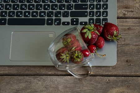 ripe strawberries and laptop on old wooden table