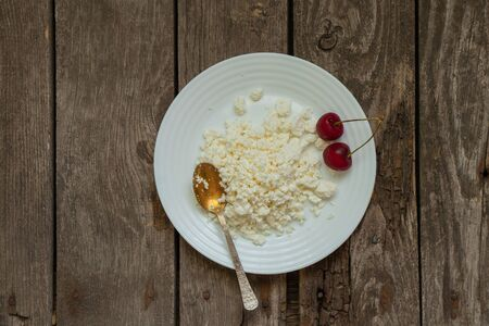 cottage cheese in a plate a table with a spoon and cherries on an old wooden table