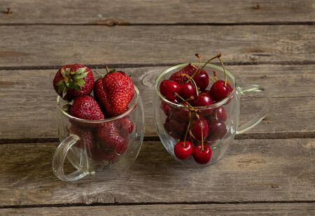 strawberries and cherries in glass cups on an old table