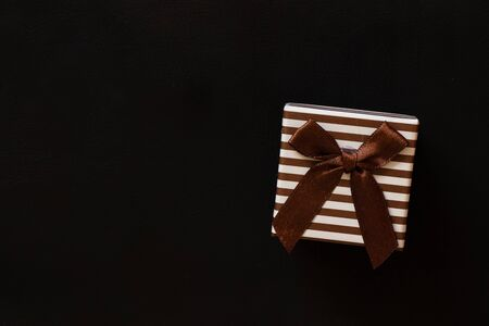 striped gift box stands on leather background Standard-Bild