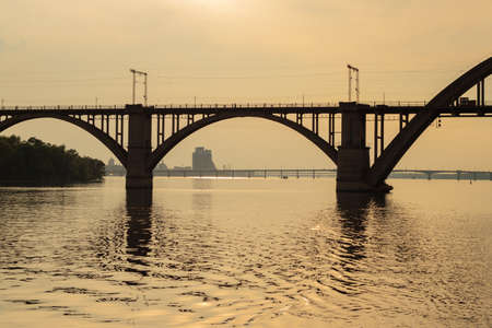 railway bridge over the Dnieper river in the city of Dnieper at sunset