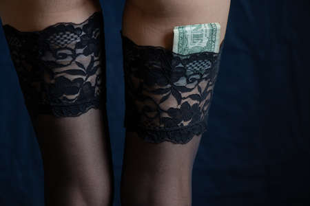 female legs in black stockings with lace and dollar bills nested in stockings on an isolated background
