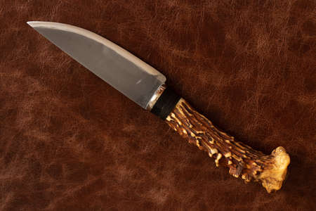 knife with a handle of a deer horn on a leather background 版權商用圖片