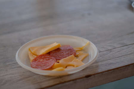 slicing cheese and sausages in a plastic plate on the table