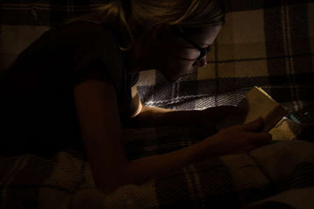 girl in the dark in the bedroom reads a book on the sofa