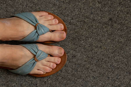 female legs in flip flops on a gray carpet in the room view from top to bottom 版權商用圖片