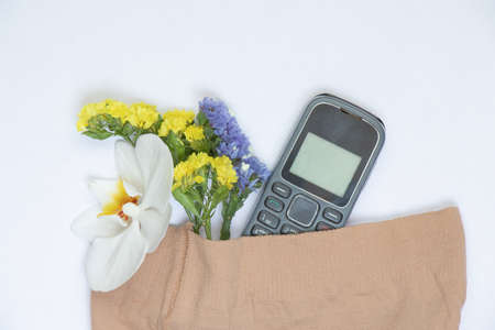 push-button telephone and blooming flowers nested in nylon tights on an isolated background