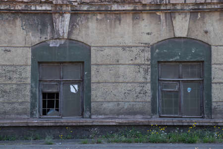 wall with windows of an old non-working factory in ukraine in the city of dnipro as a background