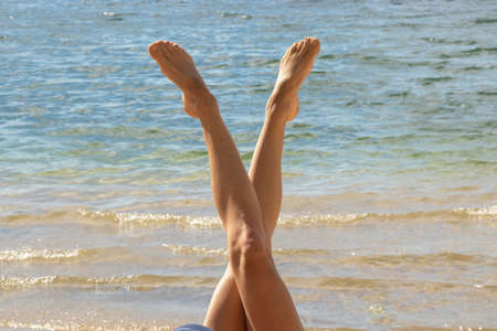 tanned legs of a young girl on a background of water in the shape of a letter v in summer