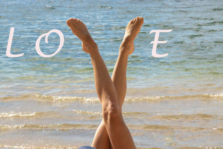 tanned legs of a young girl on a background of water in the shape of the letter v in summer on the beach with the word love in english Stock fotó