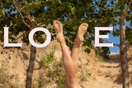 slender legs of a young girl on a background of green trees in the shape of a letter v with the word love in english Stock fotó
