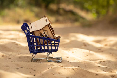 small wooden house and blue trolley with supermarket on the sand on the beach Stock fotó