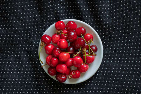 ripe red cherries on a black background