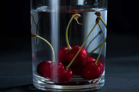 cherries in a glass of water on a black background on the table, fruit background Stock fotó