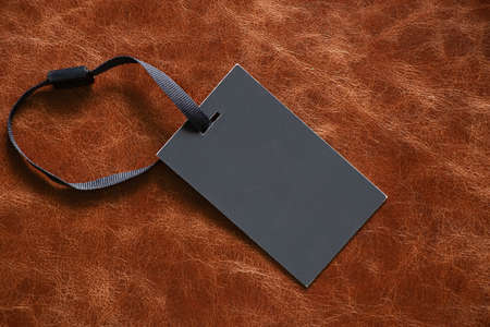 black blank price tag made of paper on a string lies on a brown leather background Stock fotó