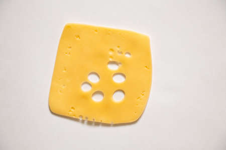 slice of hard cheese with holes on an isolated background