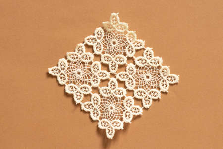 knitted white lace doily lies on a colored paper background