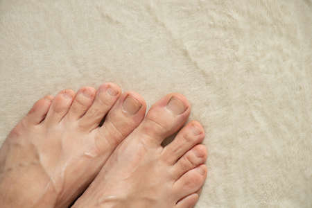 barefoot female feet stand on a white carpet at home, feet on a white background
