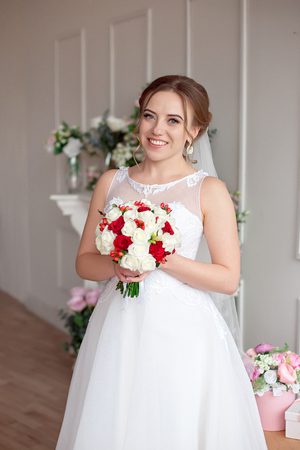 Brown-haired bride with classic wedding hairstyle, smiling taking wedding bouquet in her hands. Stock Photo