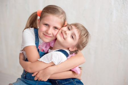 Two adorable little sisters laughing and hugging each other in studio. Great sister's love. Stok Fotoğraf