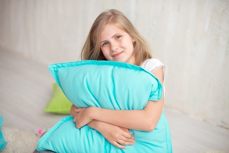 One little girl with big happy smile 10 years old sitting with pillow in living room at home Stock Photo