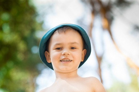 Outdoor close up portrait of little boy in a hat . Background, one person, child, 4-5 years old, happy smilling. Stock Photo