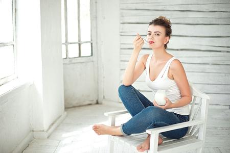 Healthy Lifestyle. Portrait Of Smiling Woman Tasting Fresh Organic Yogurt sitting in white bright room, wearing in white singlet. Stock Photo