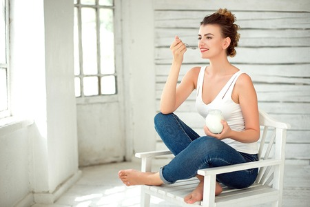 Healthy Lifestyle. Portrait Of Smiling Woman Tasting Fresh Organic Yogurt sitting in white bright room, wearing in white singlet. Stock Photo