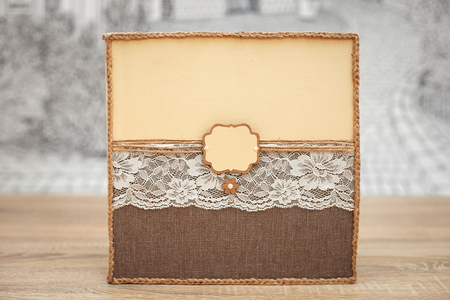 Decorated wedding guest book on the wooden table. Vintage handmade wish book with cord