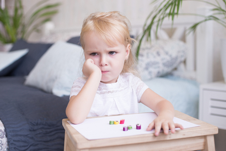 Sulky grumpy attractive little blond girl sitting with paper and crayons at a small wooden desk staring off to the side with her chin on her hand.
